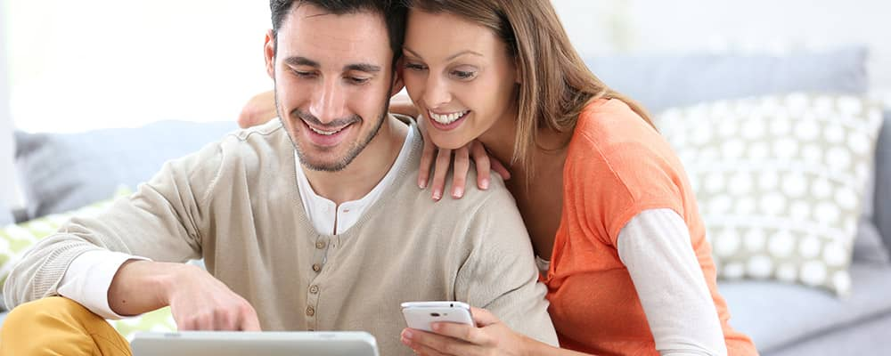couple looking at a tablet and phone