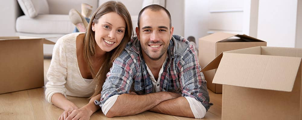 couple laying on the floor surrounded by moving boxes
