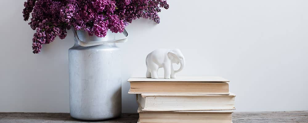 Vase next books with an elephant statue on top