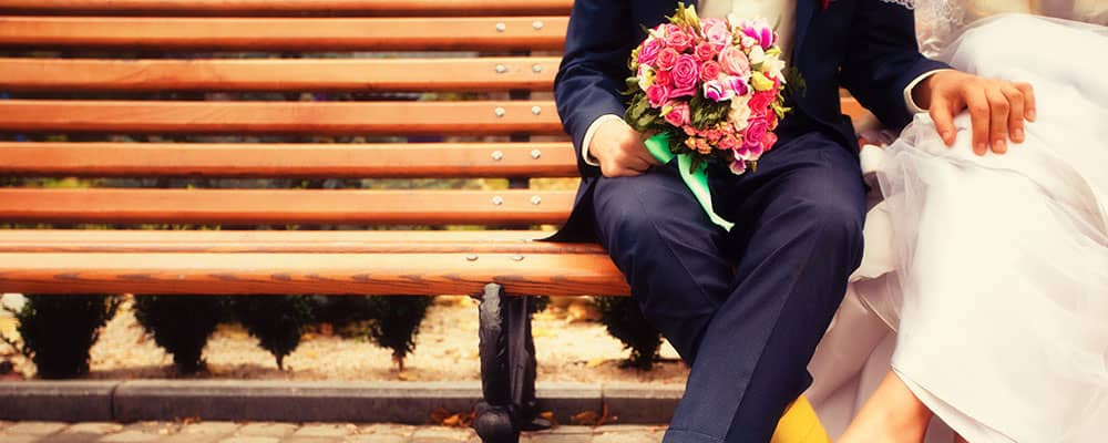 newlyweds on a bench holding hands