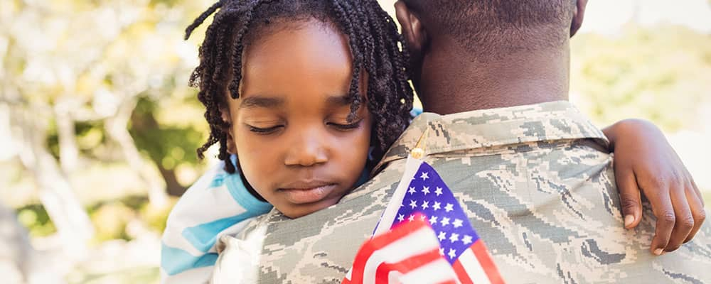small child sleeping holding an American flag in his soldier father's arms