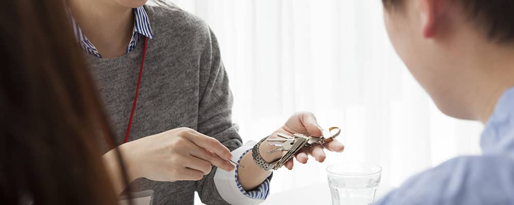 property manager handing house keys to renters