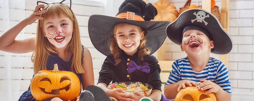 children sitting and laughing in their Halloween costumes
