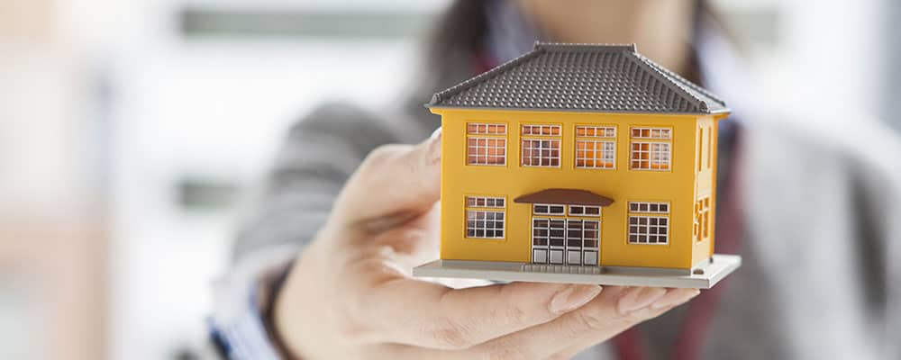 woman holding out a house model