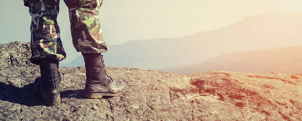 soldier standing on top of a mountain