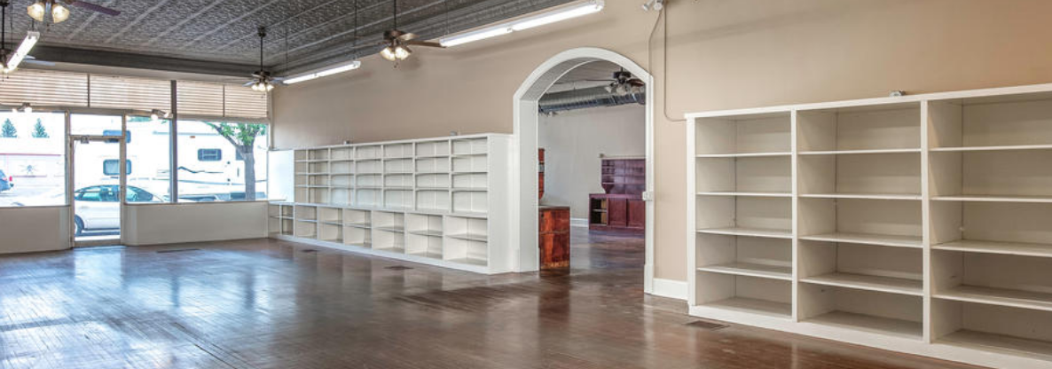 Interior image of an empty storefront with shelves.