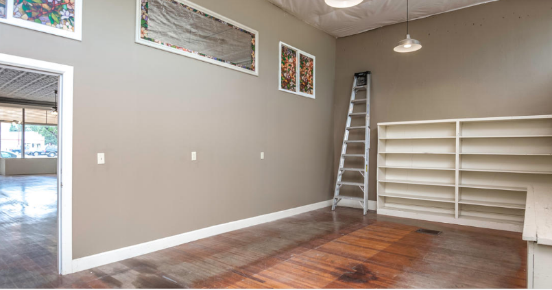 Interior image of an empty storefront with build in shelves and a ladder.