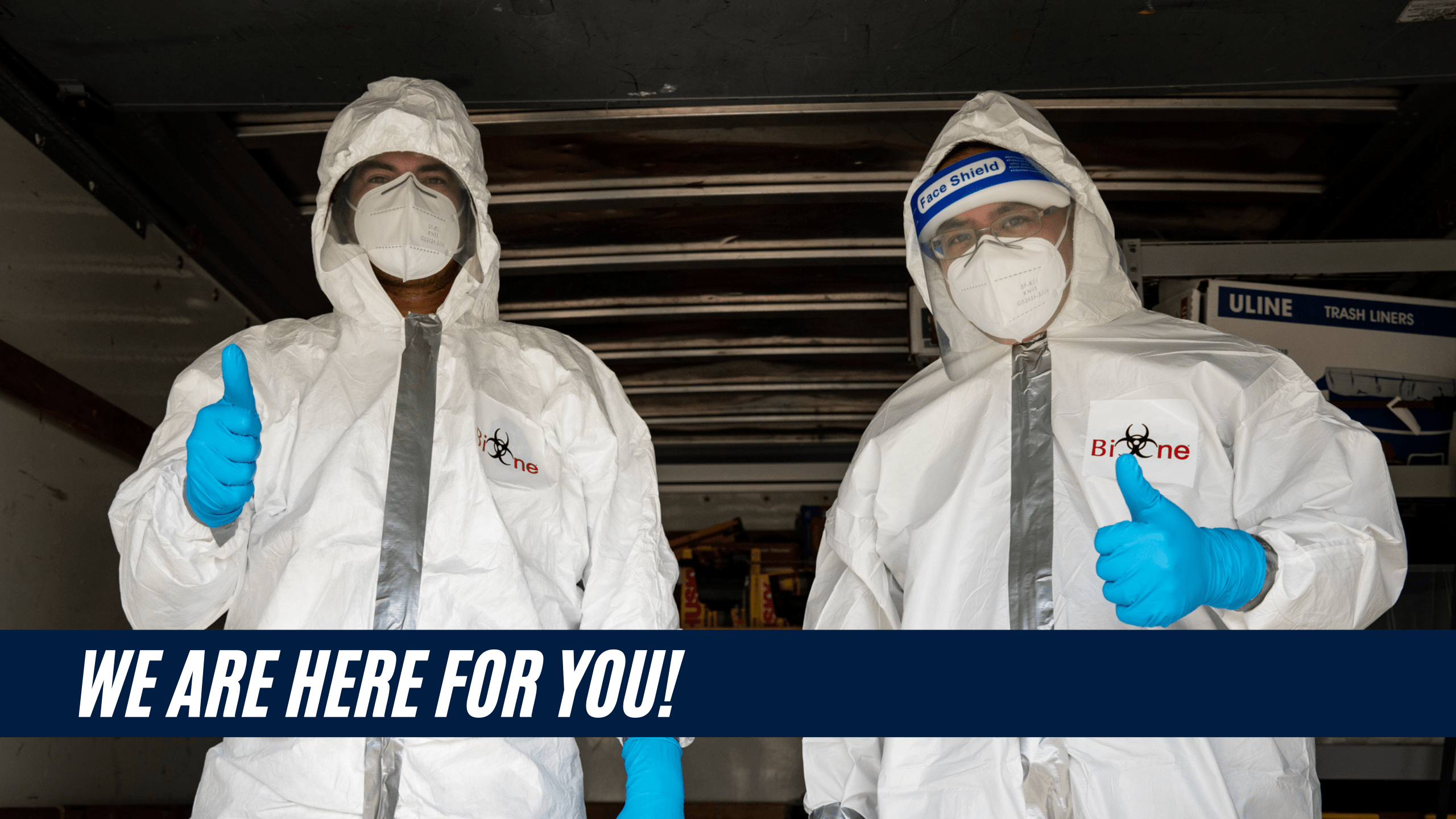 Two Bio-One service technicians dressed in white hazmat suits, N-95 masks and face shield giving a thumbs up.   We Are Here For You is on a title banner on the bottom left of the image.   Bio-One logo is on the left breast of both hazmat suits.