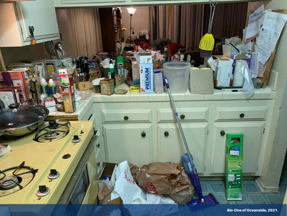 "The image shows a kitchen space packed up with filth and debris, impossible for anyone to utilize it. It has a banner on the bottom with text ""Bio-One of Oceanside, 2021."""