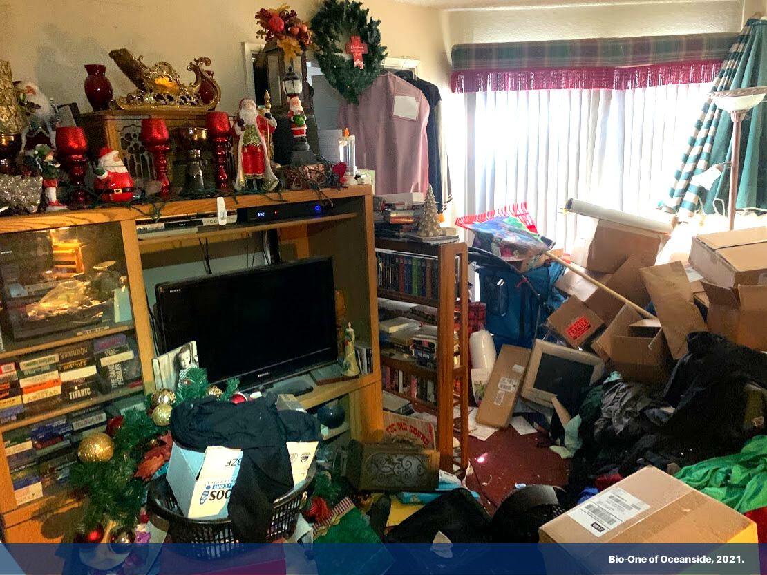 """Image shows a living room area blocked by garbage and clutter. It has a banner on the bottom with text """"Bio-One of Oceanside, 2021."""""""