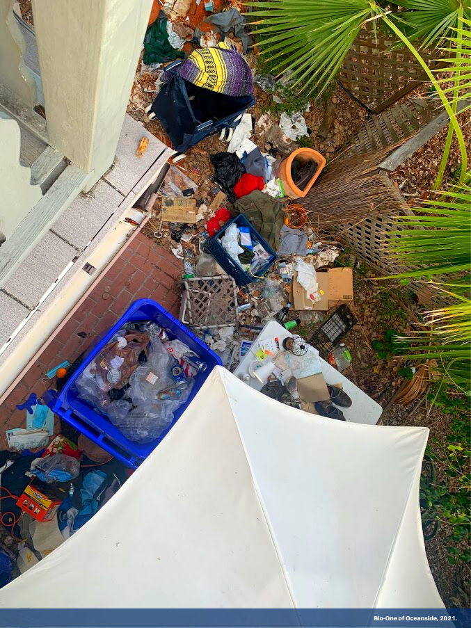 """Image show debris and trash in a Homeless Encampment, picture is taken from above. It has a banner on the bottom with text """"Bio-One of Oceanside, 2021."""""""