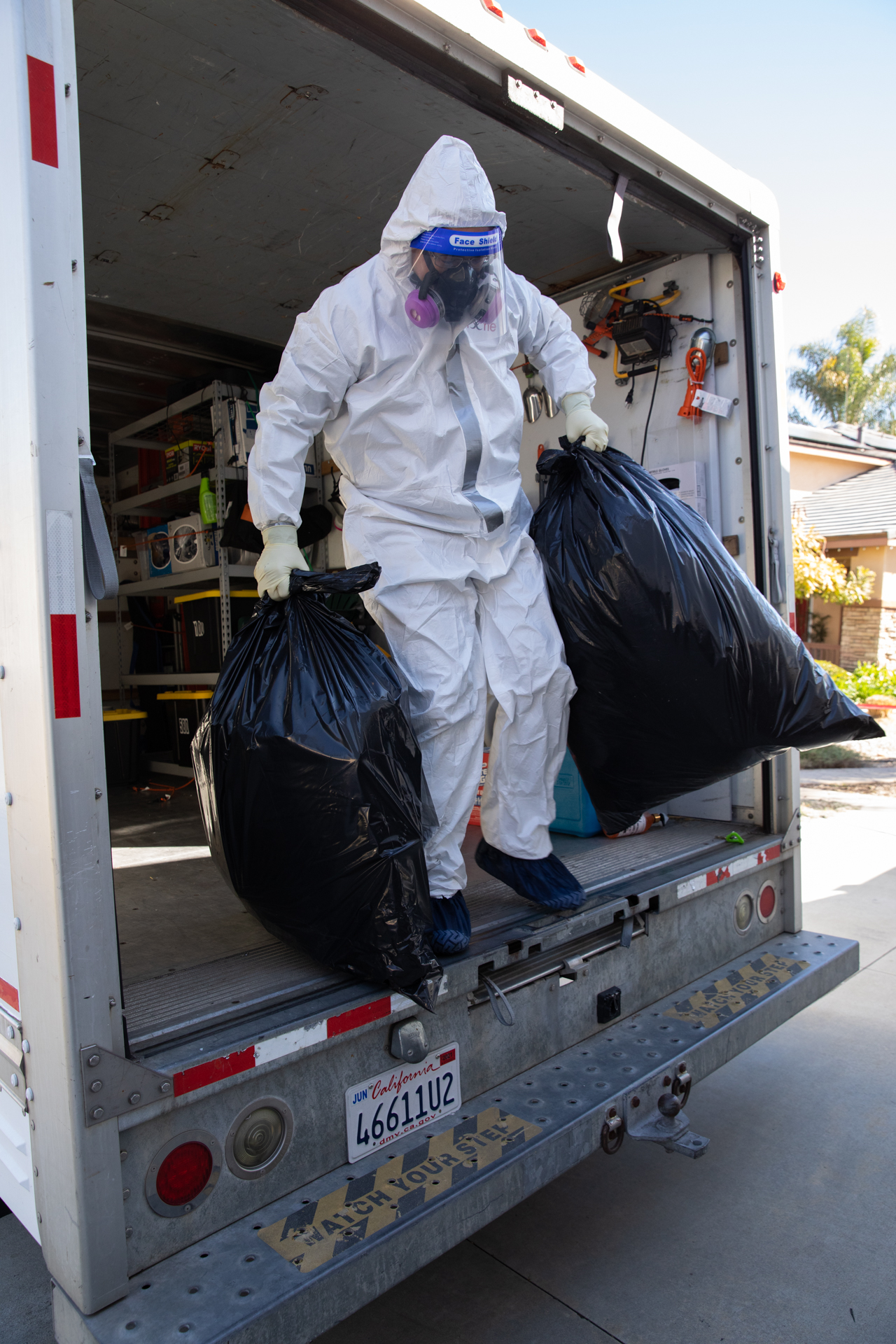 Image shows Bio-One of Oceanside technicians disposing of trash after servicing a rodent dropping scenario.