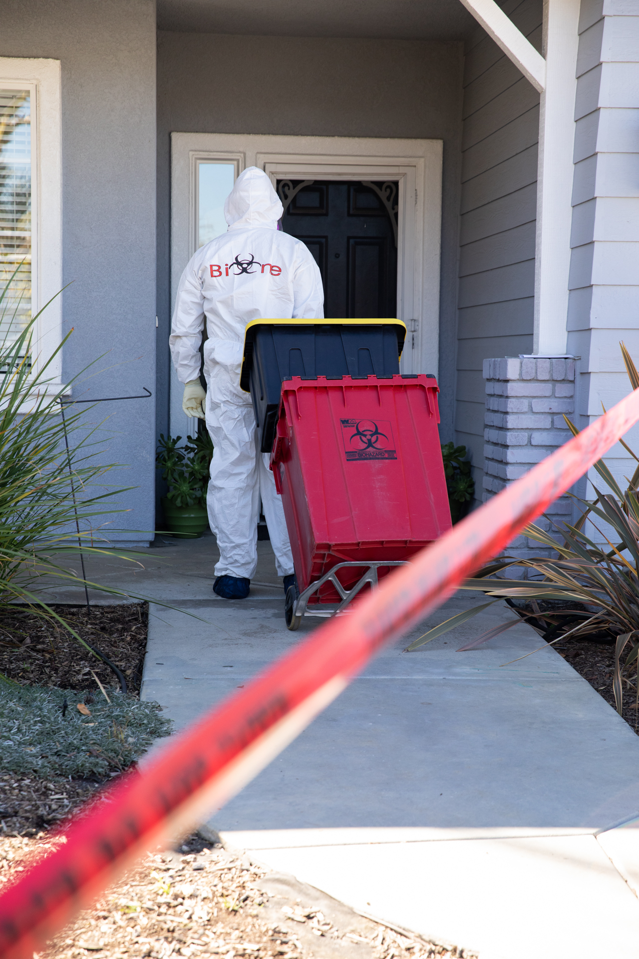 Image shows a Bio-One of Oceanside technician arriving on a scene sealed off by Police Enforcement.