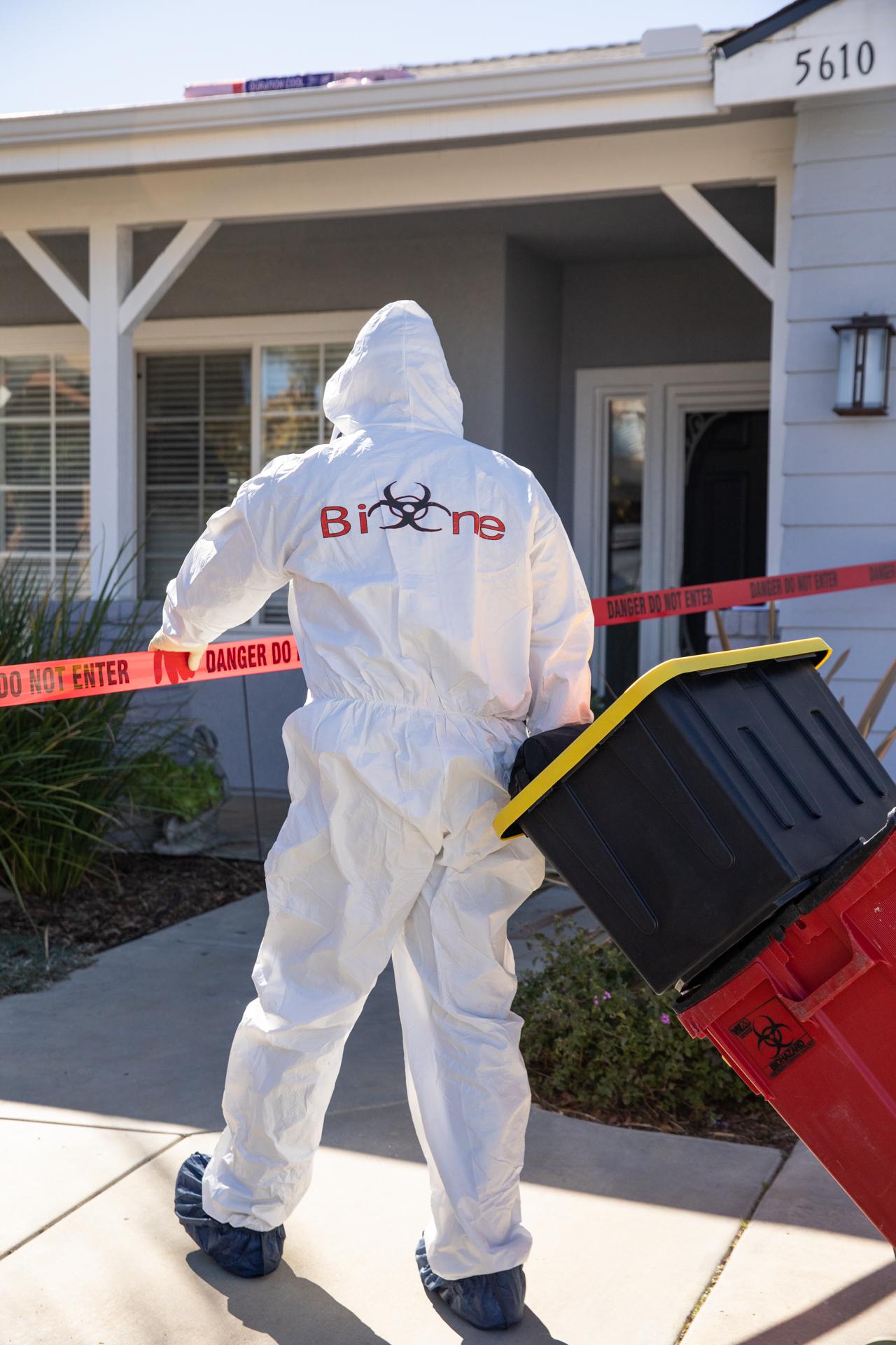Bio-One technician arriving on-scene, fully dressed in PPE.