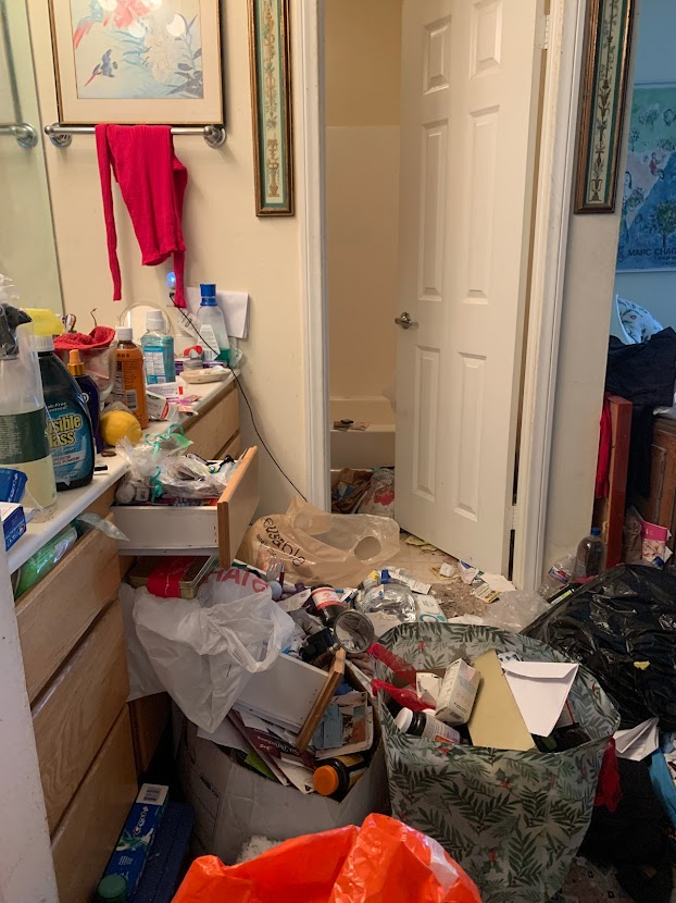 Image shows a bathroom area blocked by clutter and trash.