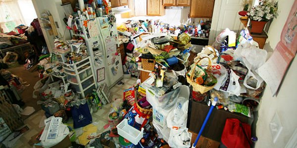 Kitchen and living room area piled with clutter.