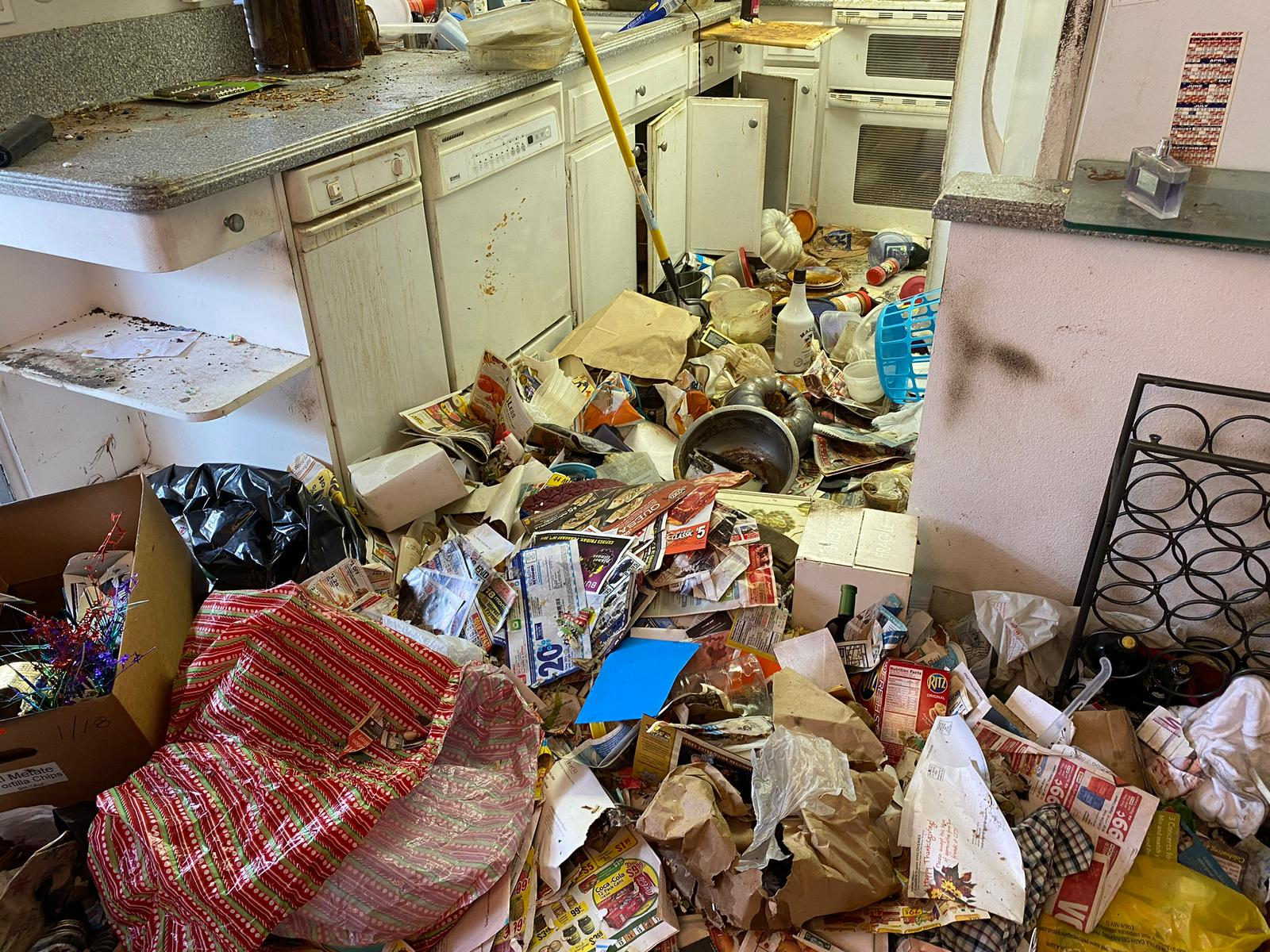Image shows a hoarding scene where the kitchen area is blocked by trash and clutter. Kitchen cabinets and space in general is completely unusable.