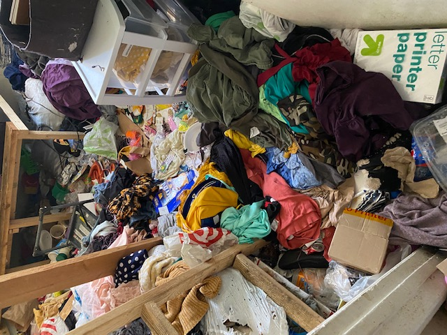 Image shows a room with an excessive amount of clothing scaretted around.