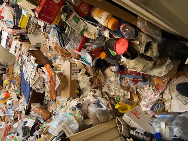 Image shows food supplies and other household items scattered around, making it impossible to walk into the room.