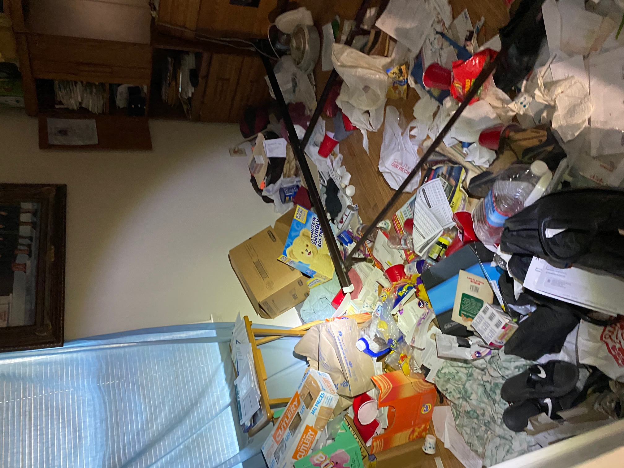 Image shows a bedroom blocked by trash and clutter. It's impossible to walk into the room.