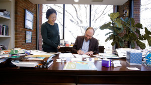 Furman's Vice President for Academic Affairs and Provost George Shields signs agreement with Sichuan University as Sichuan representative Julia Gao looks on.