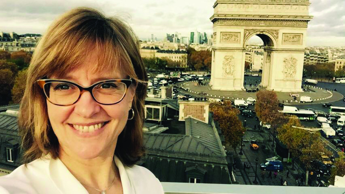 Eleanor Beardsley '86 pictured on the rooftop of the advertising firm Publicis with the Champs Élysées and the Arc de Triomphe in the background.