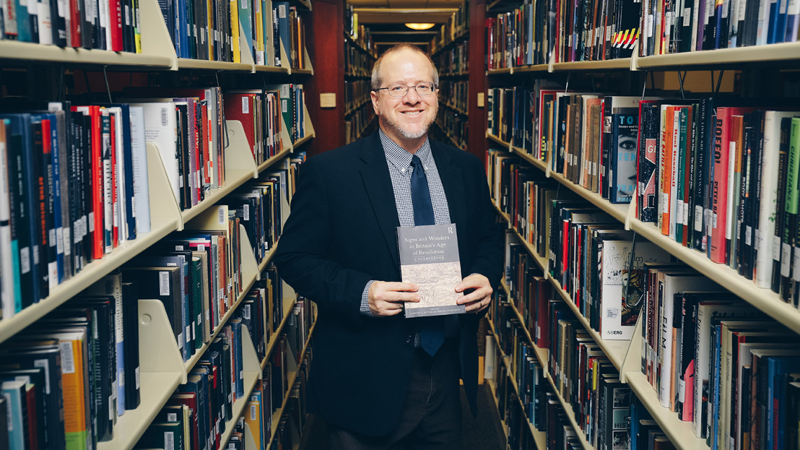 Professor of History Tim Fehler holds a sourcebook he co-authored with Abigail Hartman '17
