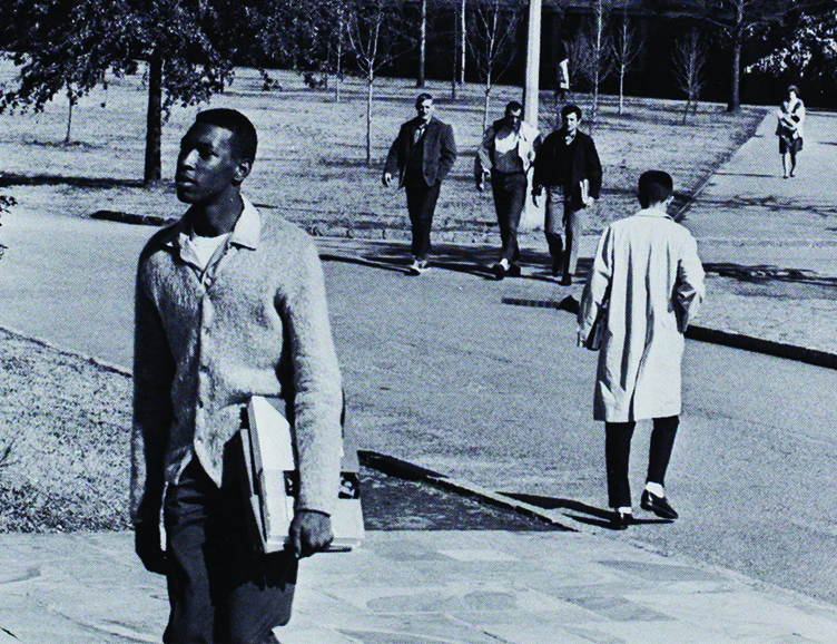 Black-and-white photo of Joseph Vaughn walking across campus. Other students are in the background.
