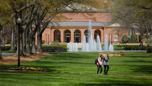 Photo of an auditorium in the distance, a fountain and two people walking across a green lawn.