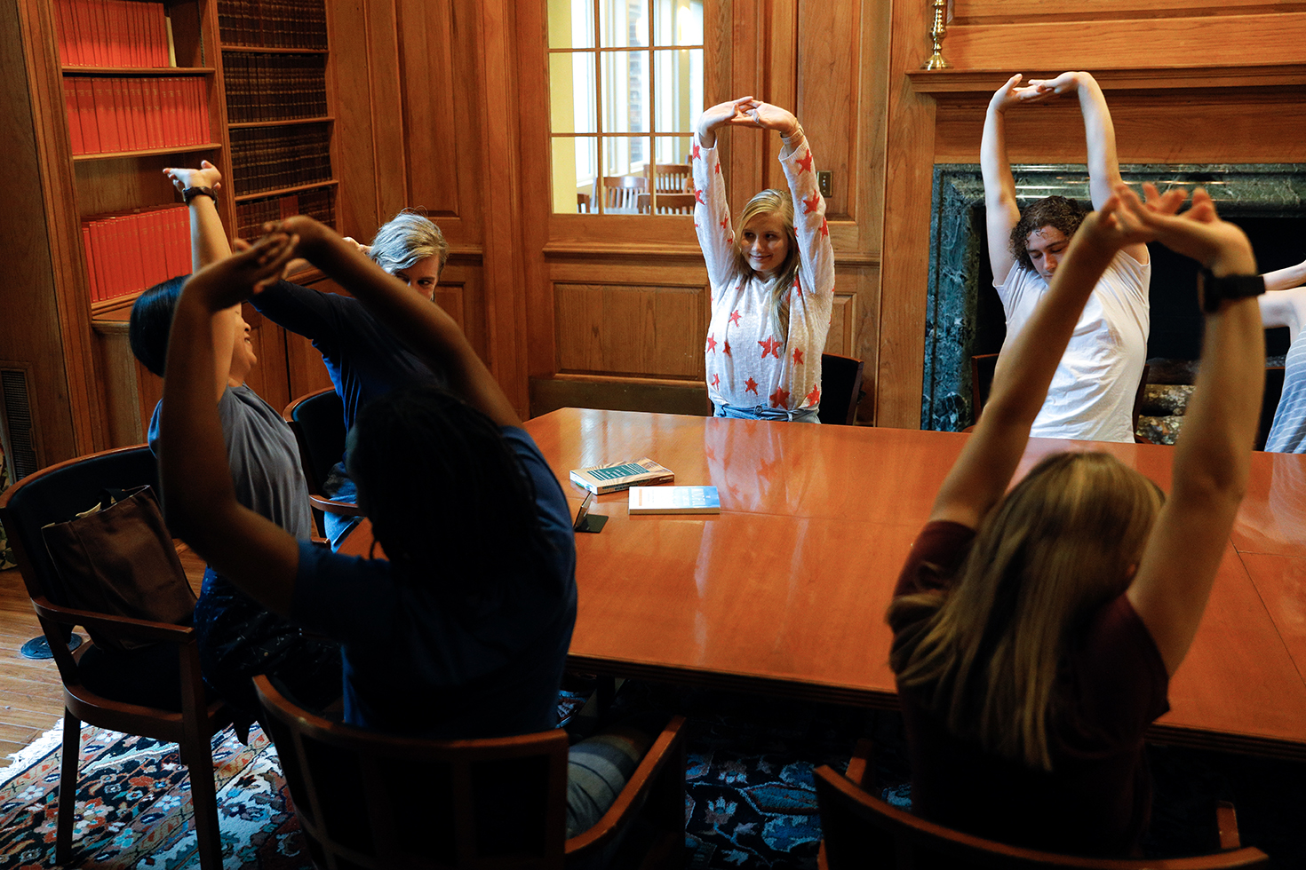 Students stretch with Furman professors Min-Ken Liao and Meghan Slinging in the James B. Duke Library's Haynsworth Room.