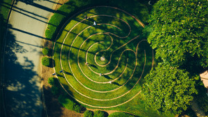 Aerial view of students walking along a large spiral in the grass.
