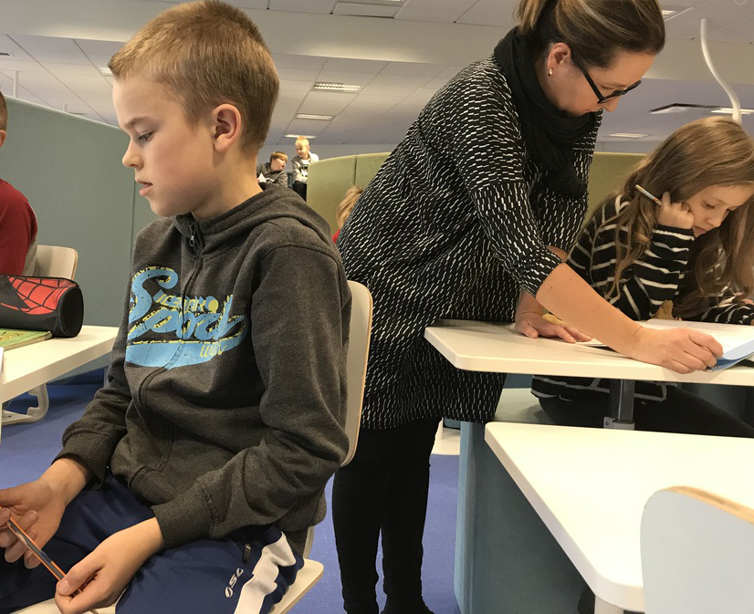 A teacher helps a fifth-grade student in a classroom and a boy sits at his desk.