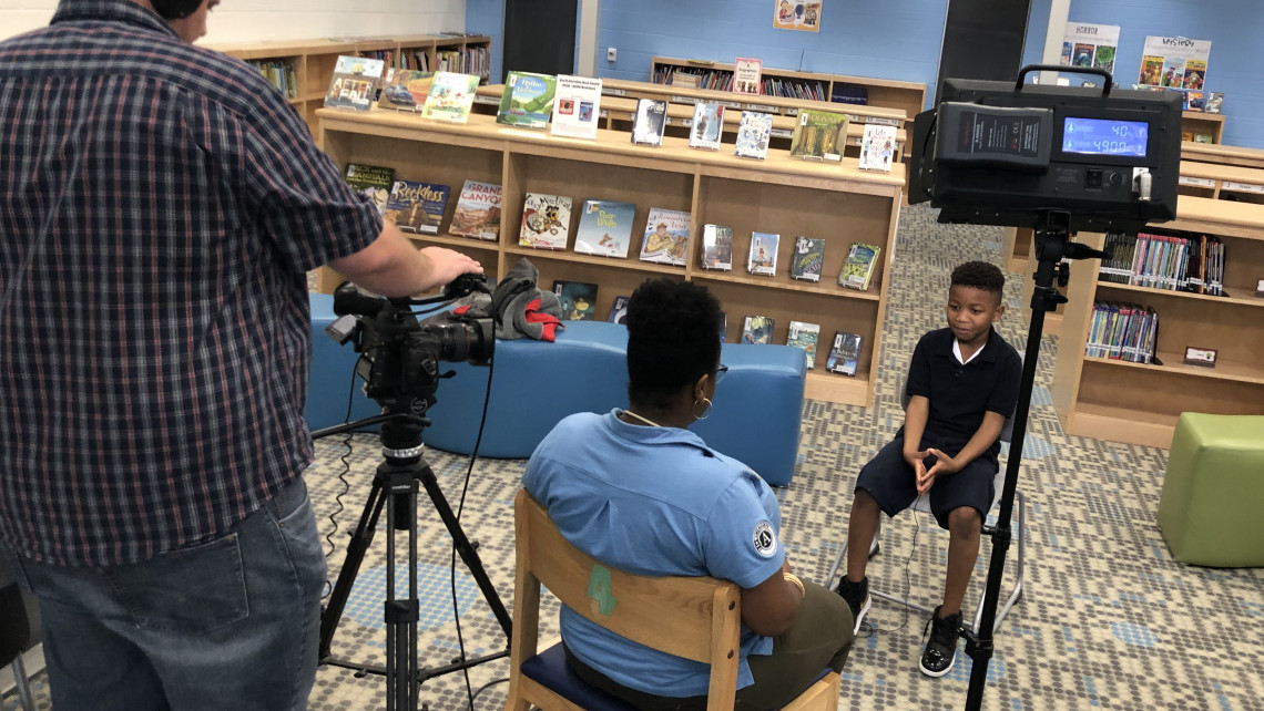 A videographer shoots an interview with a woman and a little boy in a school library.