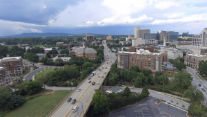A drone photo of Greenville showing part of downtown toward the mountains.