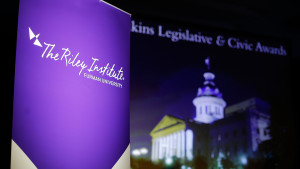 Photo of a purple Riley Institute banner with the state capital building behind.