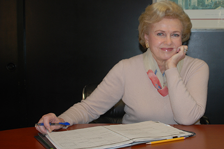 A portrait of a woman at a table with her desk calendar open.