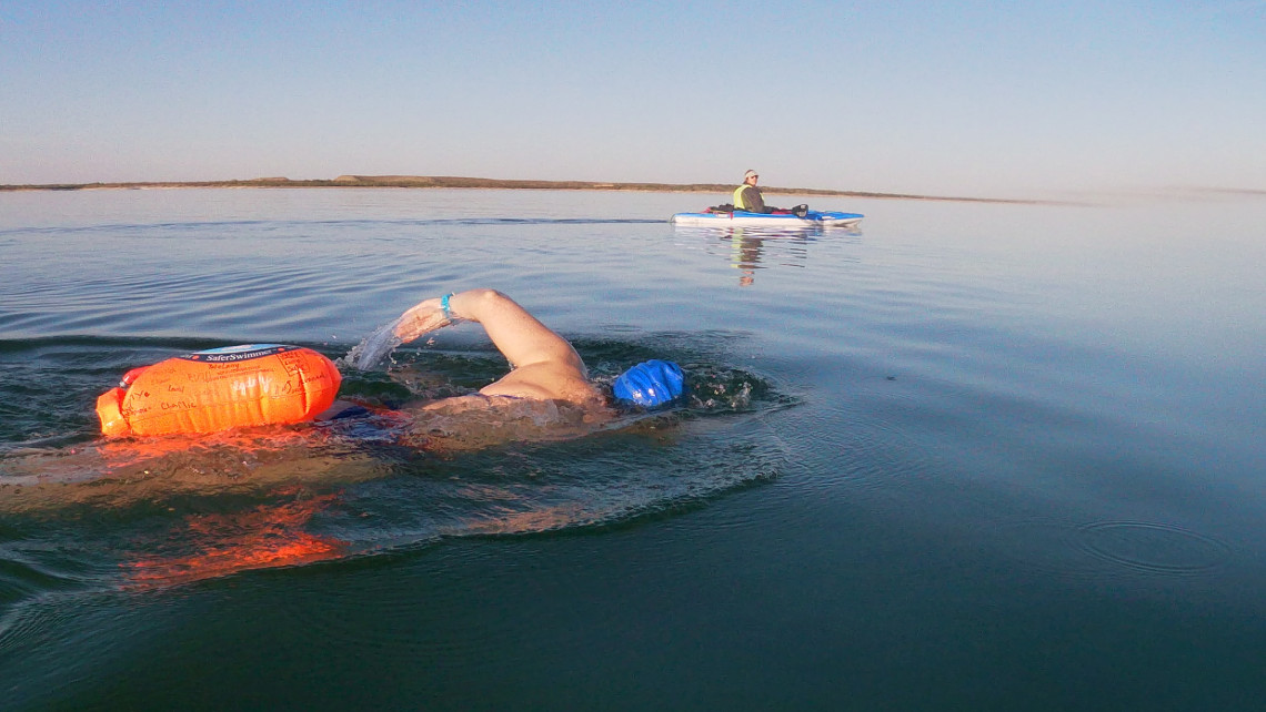 A swimmer plows through the blue water of a lake as a kayaker looks on in the distance.
