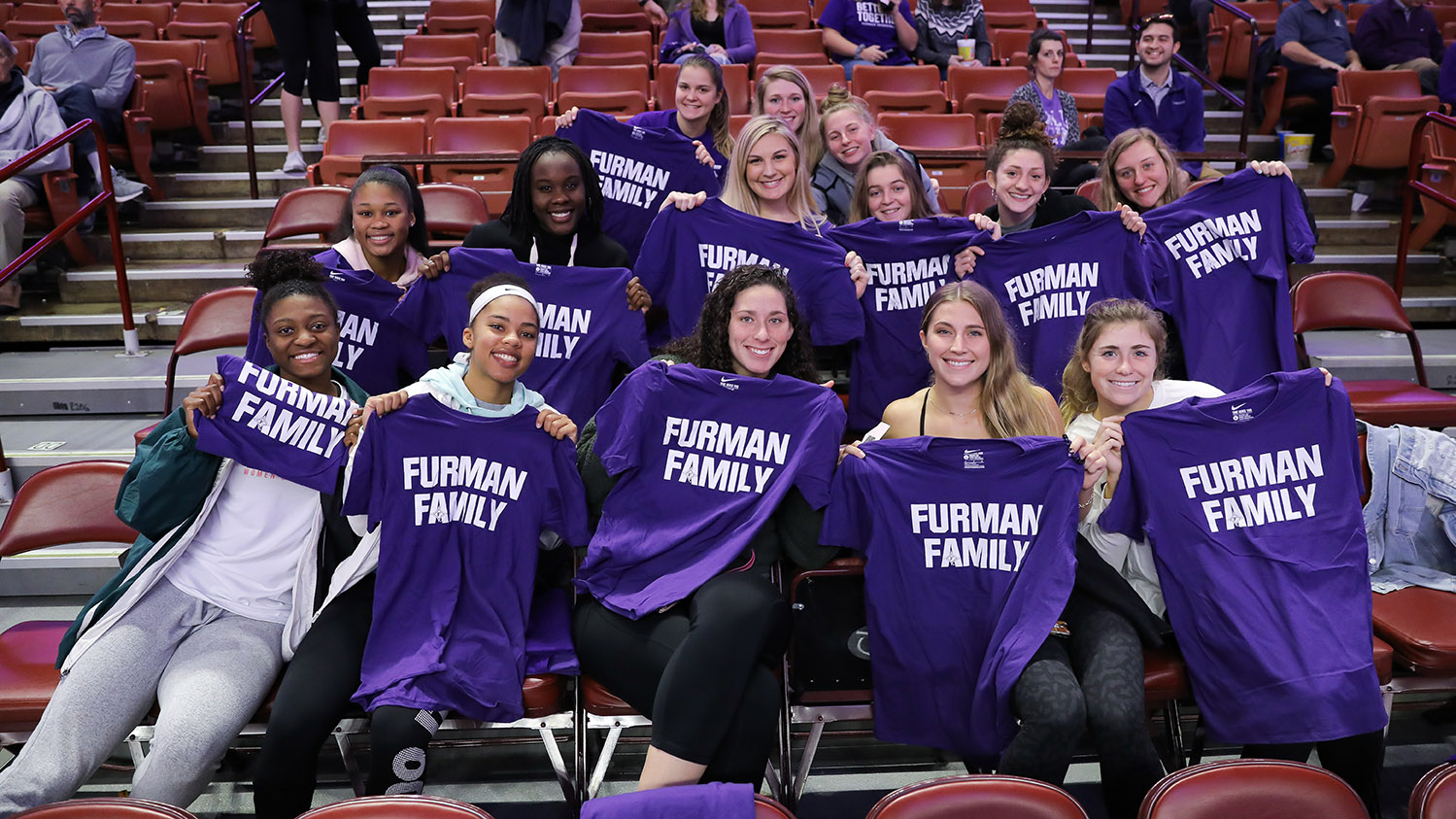 Furman students hold matching T-shirts at a Weekend at the Well game