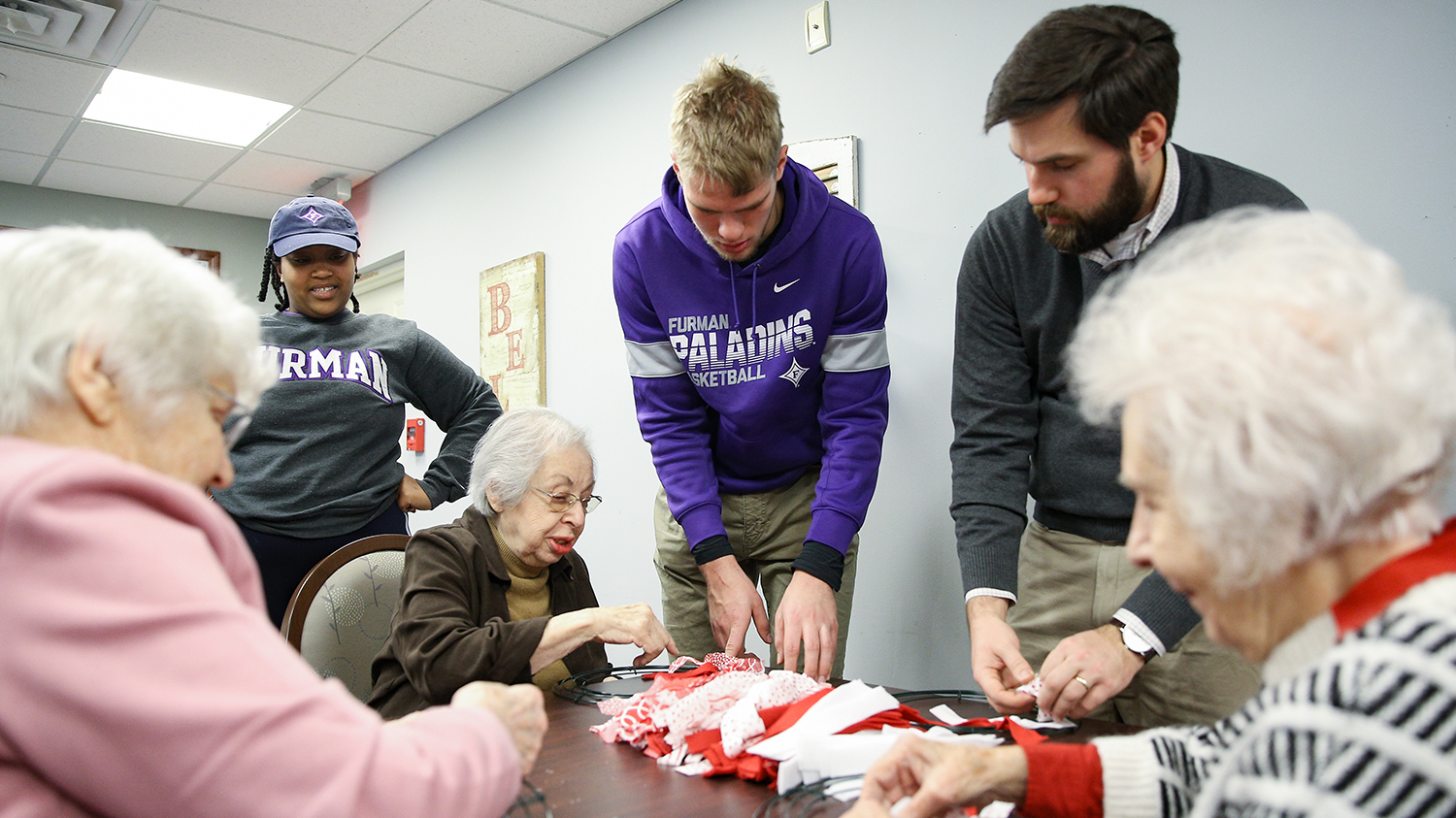 Students work with senior citizens.