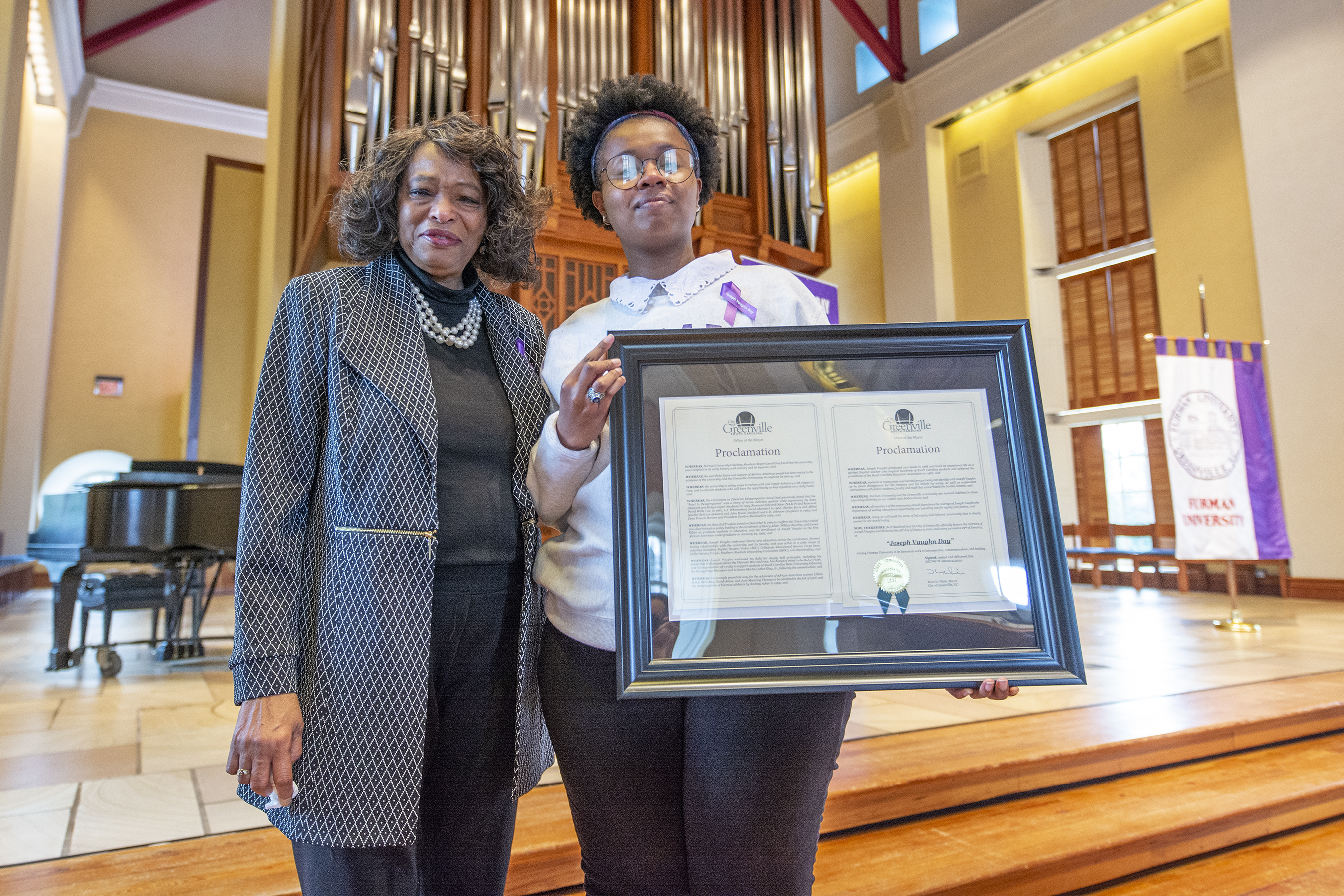 Adare Smith '20 holds a framed print of the city of Greenville's Joseph Vaughn Day Proclamation with Lillian Brock Flemming '71 to her left