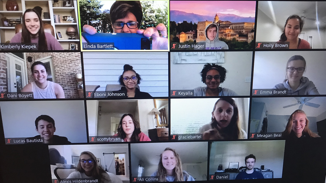 A screen shot of a Zoom class with photos of 15 people arranged in a grid.