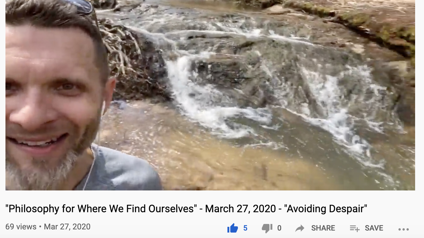 A man with a goatee shoots a video selfie in front of a large creek with rapids.