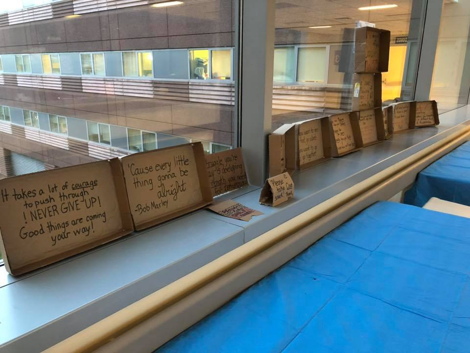 Words of inspiration are written on small cardboard signs lined up along a window sill.