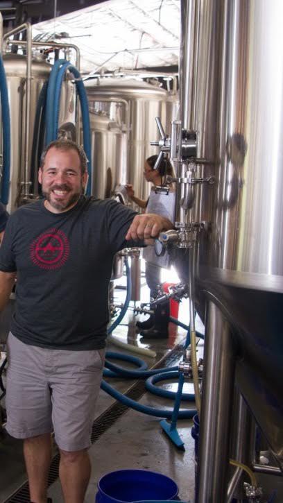 Brad Casanova '03, M'05 stands next to a beer fermenter