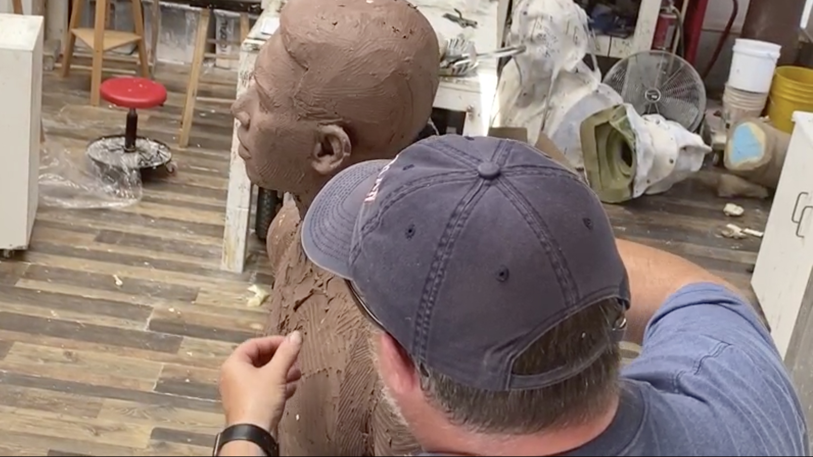 Photo of a sculptor working on a clay sculptor of a man.