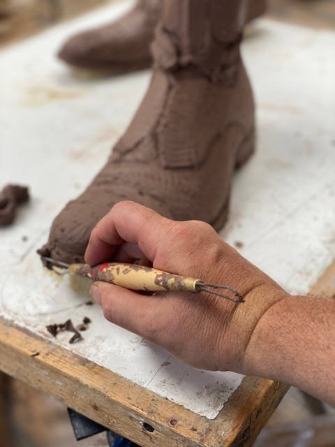 Close-up photo of a sculptor creating a shoe in clay.