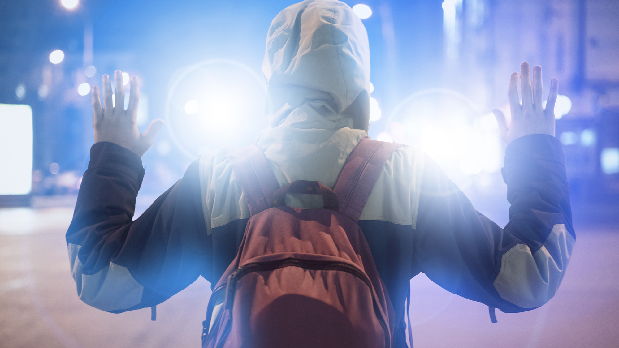 Stock photo of a person with a backpack, wearing a hoodie, with hands up.