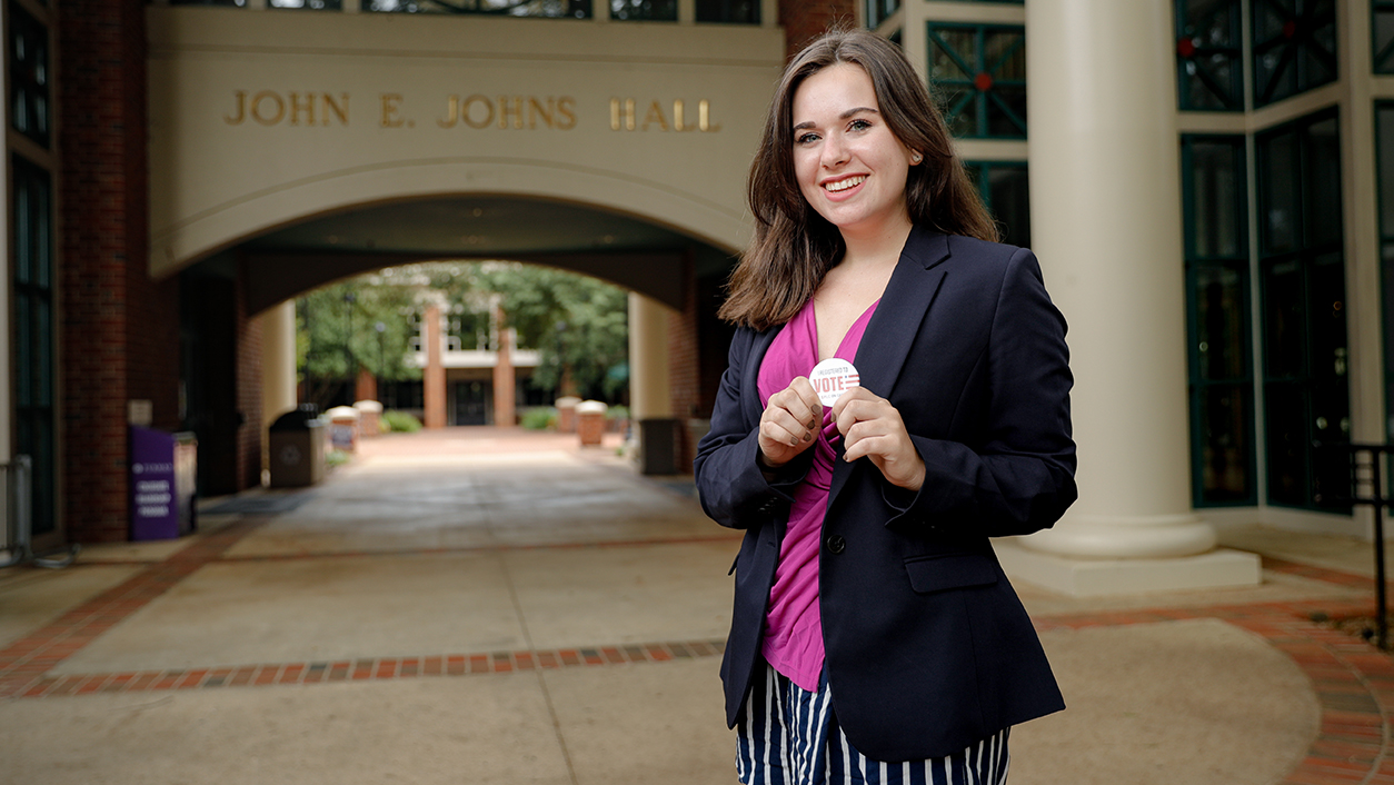 Erica Daly '22 holds a Dins Vote pin in front of Johns Hall