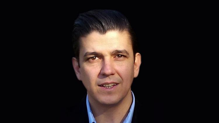 man in black jacket, blue shirt, Akan Malici