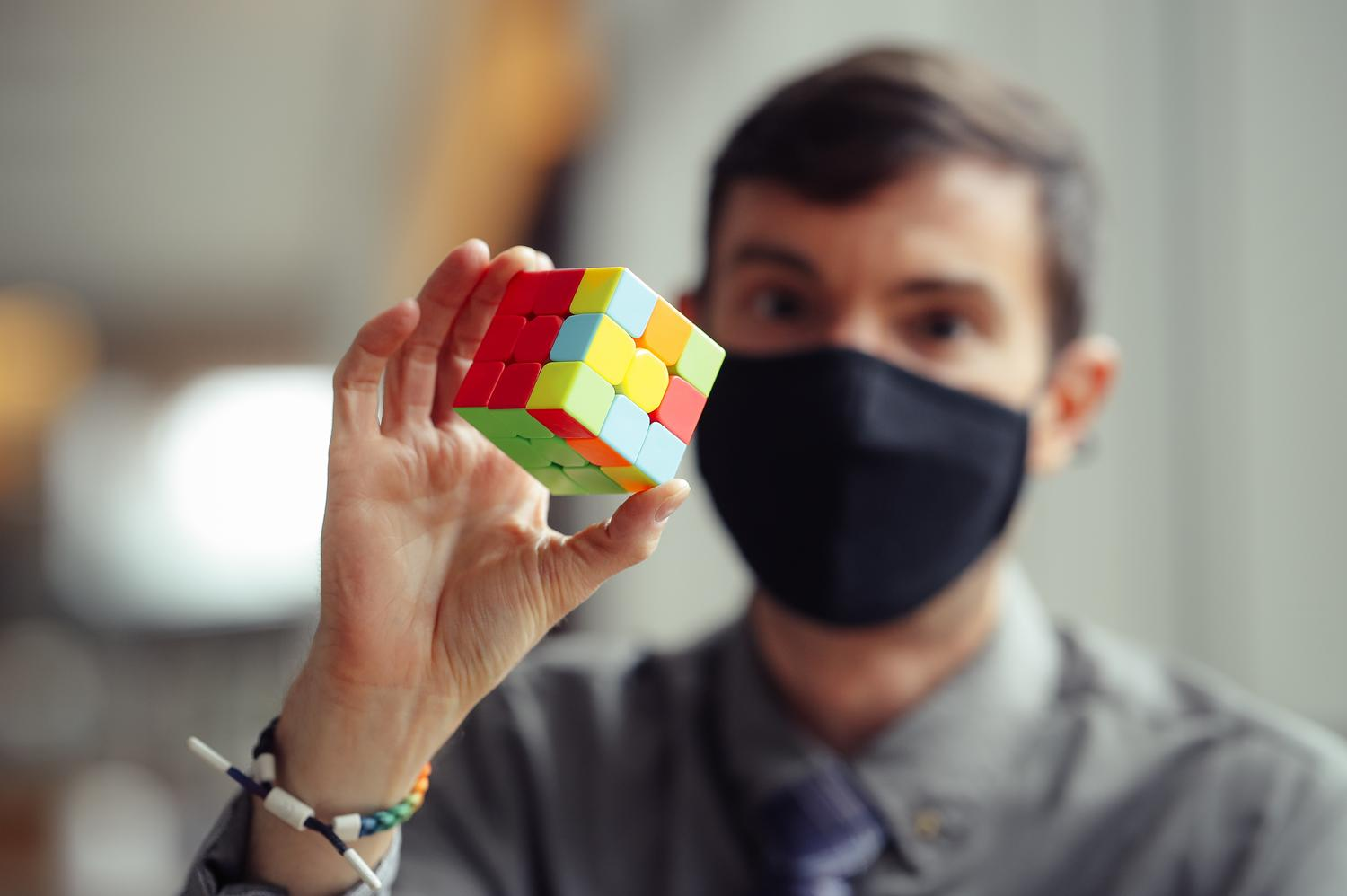 man in mask holds Rubik's cube puzzle